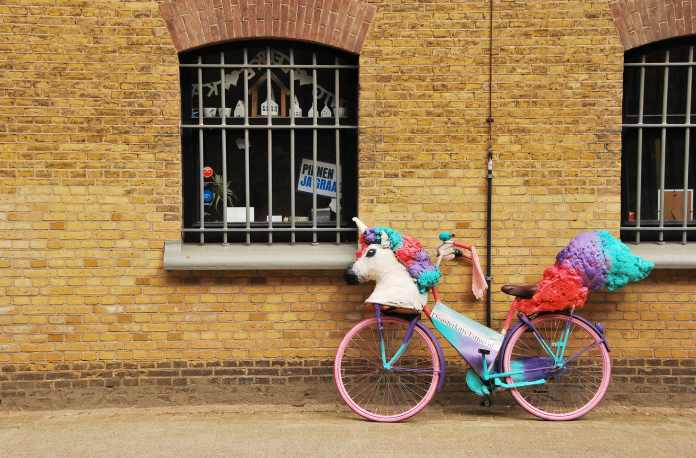 Bicycle decorated with unicorn head and LGBT colors.