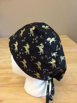 Black scrub hat for adults with golden unicorns on it.
