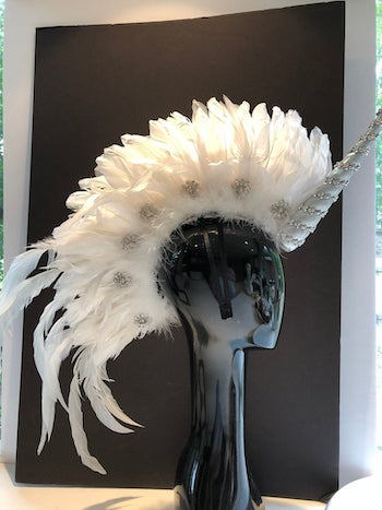 Headpiece of a unicorn party covered with feathers and with a silver unicorn horn.
