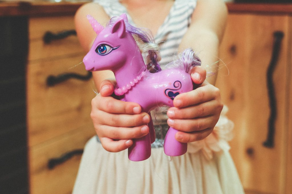 A child holding a unicorn toy which got inspired by My Little Pony.