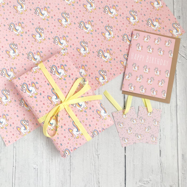Pink unicorn wrapping paper with cartoon unicorns and stars