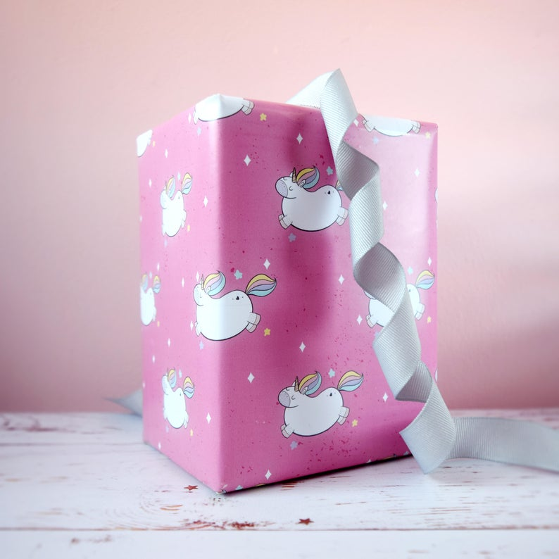 Pink gift wrapping paper with chubby cartoon unicorns